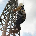 worker climbing vertical tower wearing fall protection